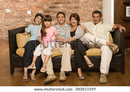 Family sitting on sofa - stock photo