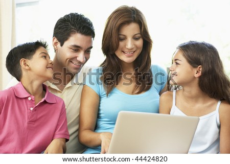 Family Sitting On Sofa At Home With Laptop - stock photo
