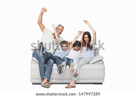 Family sitting on sofa raising their arms on white background