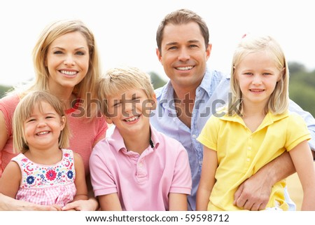 Family Sitting On Straw Bales In Harvested Field - stock photo