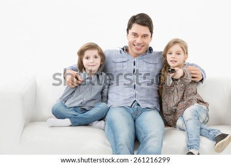 Family sitting on the couch watching television, a girl holding a remote control on a white background - stock photo