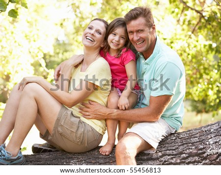 Family Sitting On Tree In Park - stock photo