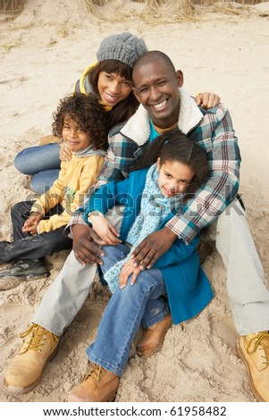 Family Sitting On Winter Beach - stock photo