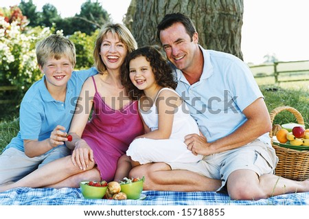 Family sitting outdoors with picnic smiling - stock photo