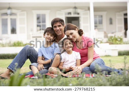 Family Sitting Outside House On Lawn - stock photo