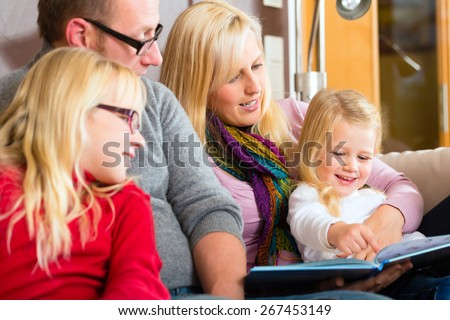 Family sitting together with mother, father and children comfortable on sofa, listening to fairy tale from story book - stock photo
