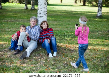 Family sitting under tree in park when little girl making picture with cellphone - stock photo