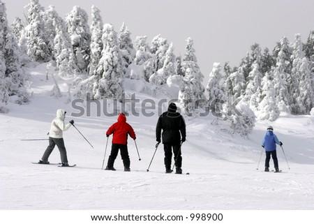 Family Skiing Downhill - stock photo