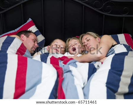 Family sleeping in the same bed - stock photo