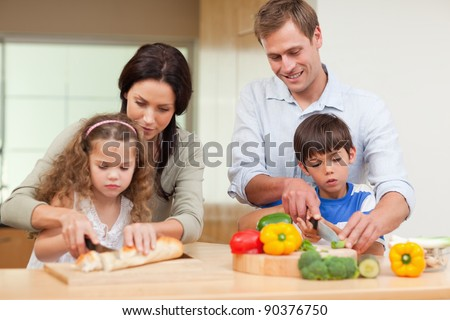 Family slicing ingredients together - stock photo