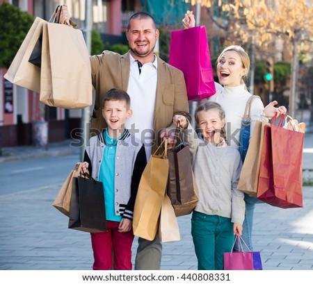 Family smiling and holding shopping bags in the town  - stock photo