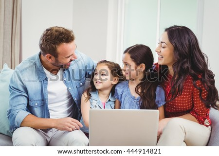 Family smiling and using laptop while sitting on sofa at home