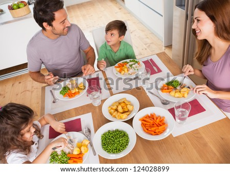 Family smiling around a healthy meal in kitchen - stock photo