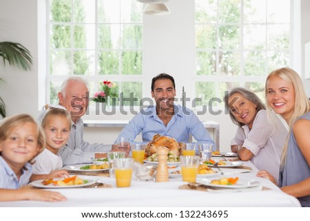 Family smiling around the dinner table at thanksgiving - stock photo