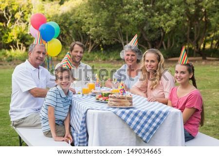 Family smiling at camera at birthday party outside at picnic table - stock photo