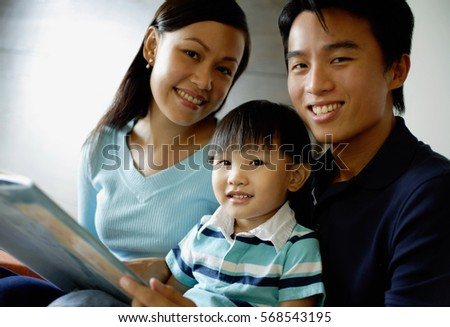 Family smiling at camera, father holding a book