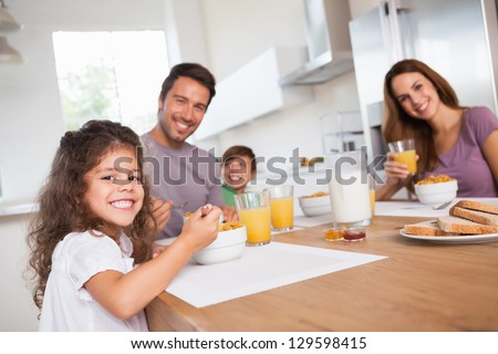 Family smiling at the camera at breakfast in kitchen - stock photo