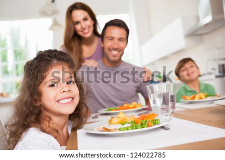 Family smiling at the camera at dinner table in kitchen - stock photo