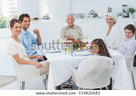 Family smiling at the dinner table and looking at camera - stock photo