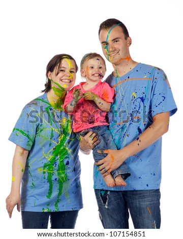 Family smiling for the camera with paint splattered all over their clothes after having a paint fight.