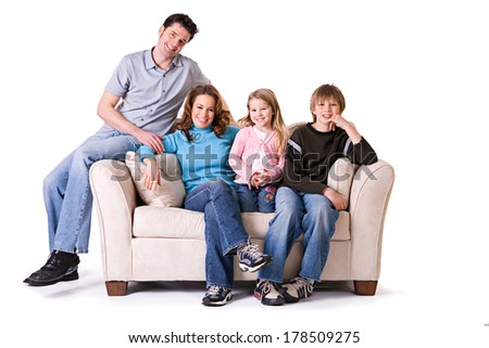 Family: Smiling Nuclear Family Sitting On Couch - stock photo