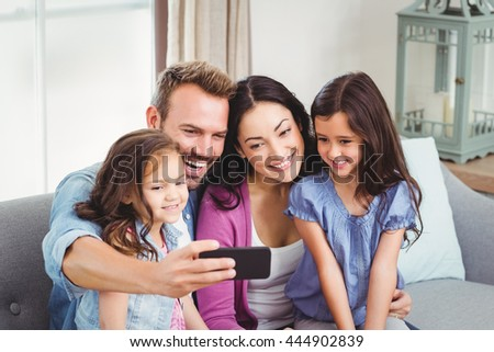 Family smiling while taking selfie on mobile phone at home - stock photo