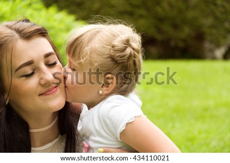 family spends time in nature. daughter gently kisses mother