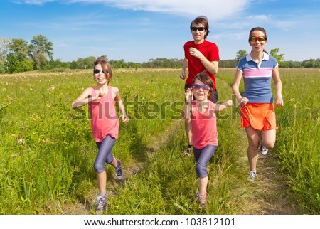 Family sport, jogging outdoors. Happy active parents with kids run. Healthy family lifestyle concept - stock photo