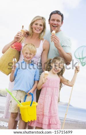 Family standing at beach with ice cream smiling - stock photo