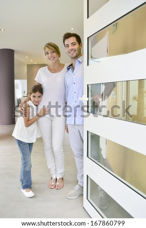 Family standing at front door to invite people in - stock photo