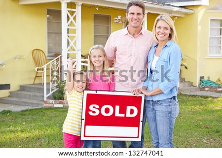 Family Standing By Sold Sign Outside Home - stock photo