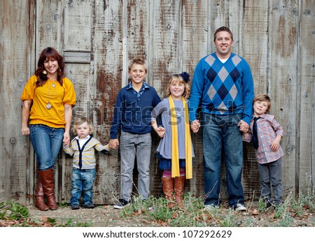 Family standing in front of a wooden fence - stock photo