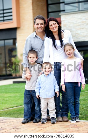 Family standing in front of their house and smiling - stock photo