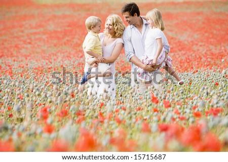 Family standing in poppy field smiling - stock photo