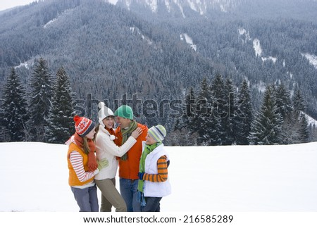 Family standing in snow on mountain top - stock photo