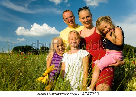 Family standing in the grass at a wonderful summer day - stock photo