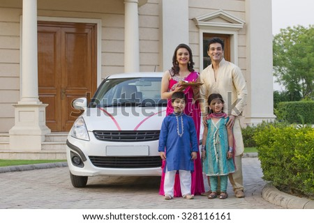 Family standing next to new car - stock photo