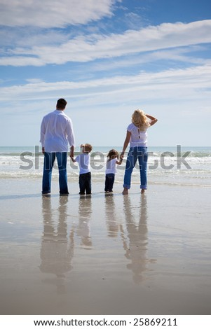 Family standing on a beach, looking at the ocean.