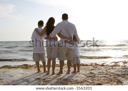 Family standing on a beach, looking towards water - stock photo