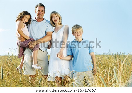 Family standing outdoors holding hands smiling