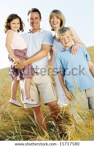 Family standing outdoors smiling - stock photo