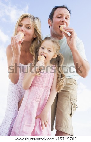 Family standing outdoors with ice cream - stock photo