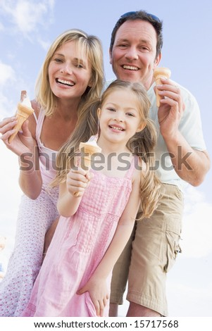 Family standing outdoors with ice cream smiling - stock photo