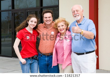 Family standing outside their polling place wearing I Voted stickers.  (stickers are generic ones, not trademarked) - stock photo