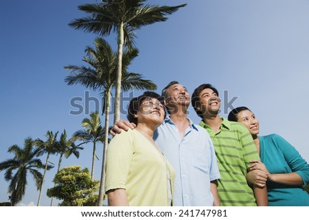 Family Standing Under Palm Trees - stock photo