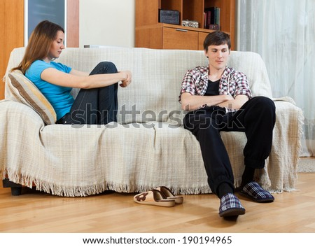 Family stress. Sad guy and girlfriend after quarrel  in living room at home - stock photo