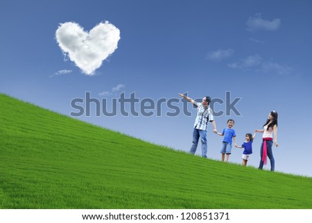 Family stroll in park under heart clouds - stock photo