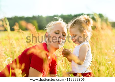 Family summer - blowing dandelion seeds in sunshine