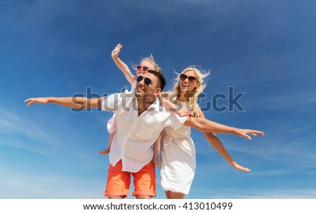 family, summer vacation, adoption and people concept - happy man, woman and little girl in sunglasses having fun over blue sky background - stock photo