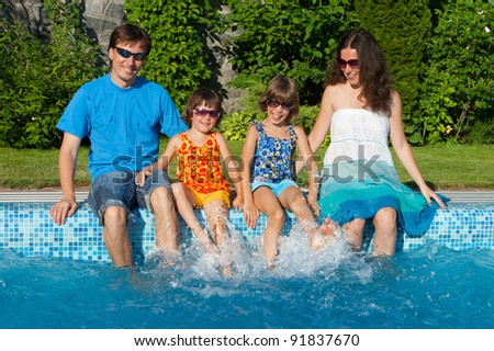 Family summer vacation. Happy parents with two kids having fun and splashing near swimming pool